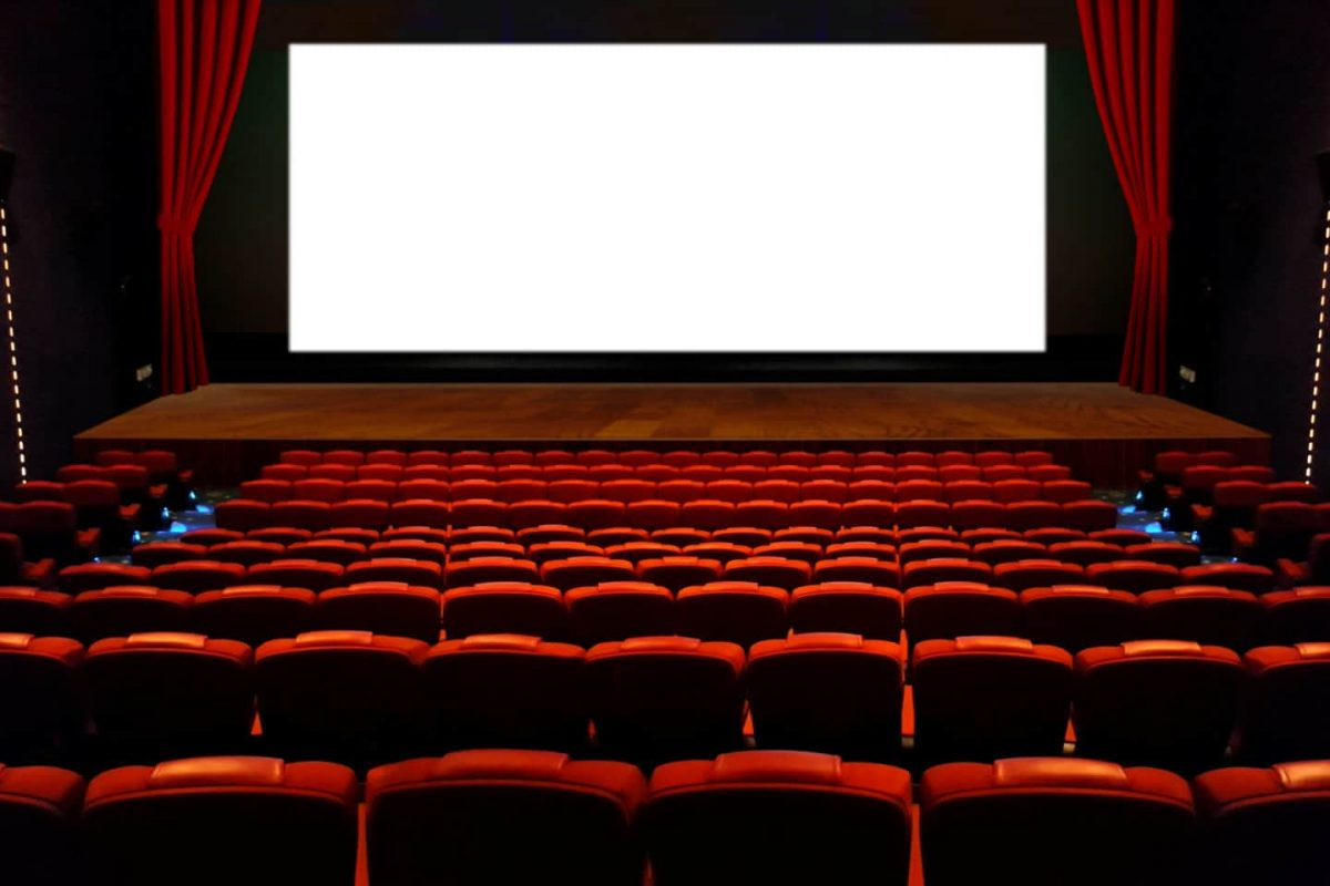 Empty cinema hall with red seats and big wide screen